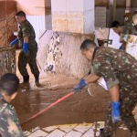 Bombeiros trabalham na assistência aos desabrigados.